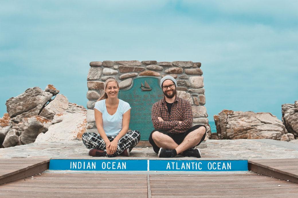 Zwei Menschen sitzen am Südlichsten Punkt Südafrikas, der Atlantik und Indische Ozean treffen hier aufeinander