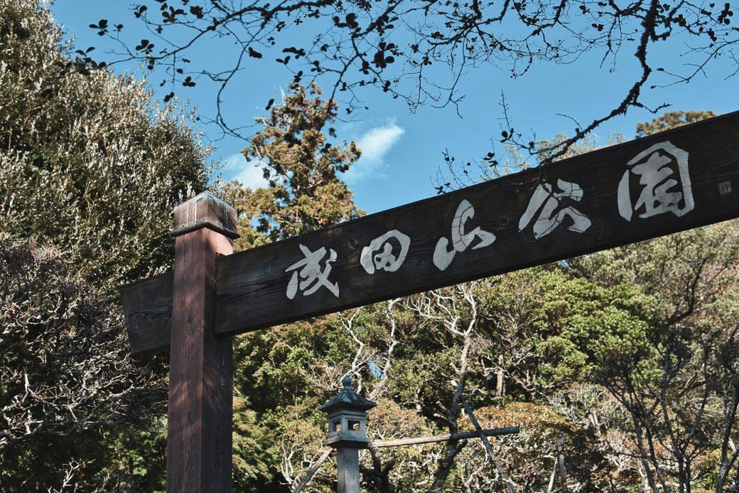 Japanisches Eingangstor mit Schriftzeichen. Im Hintergrund Wald