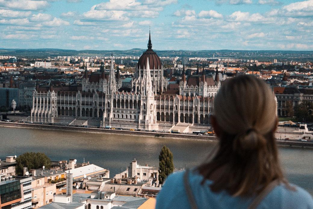 Frau schaut auf das Parlament in Budapest. Schöner Ausblick.