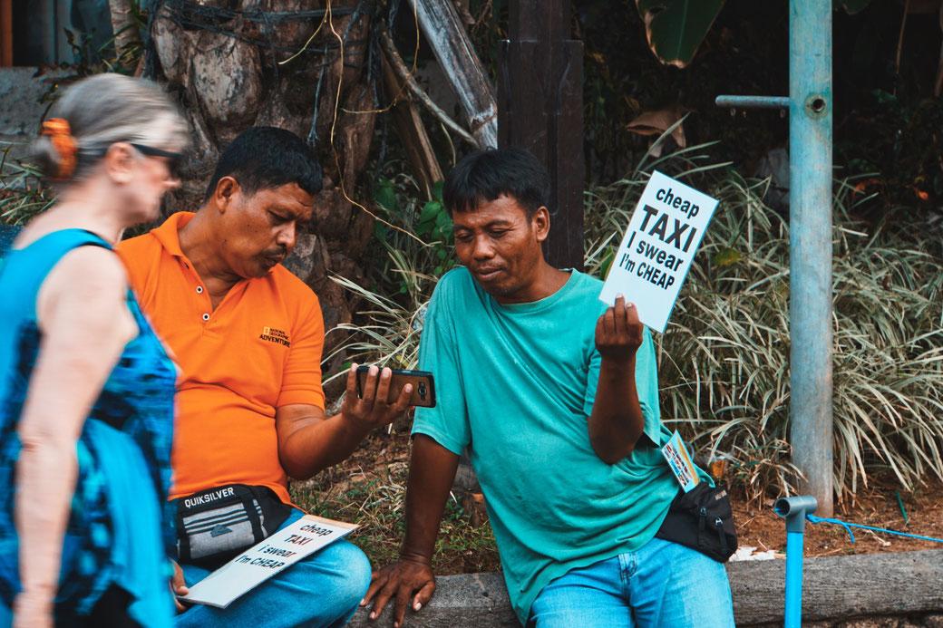 Taxifahrer in Ubud halten werbeschild hoch und gucken dabei aufs Handy