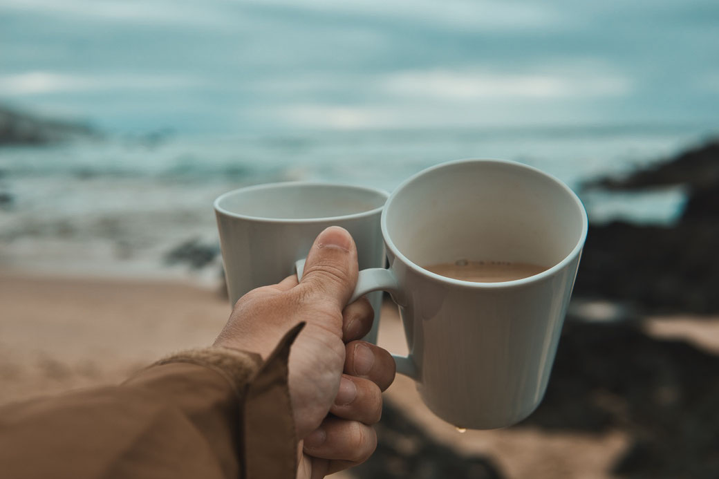 Zwei Kaffeetassen, halb gefüllt mit Kaffee am Strand
