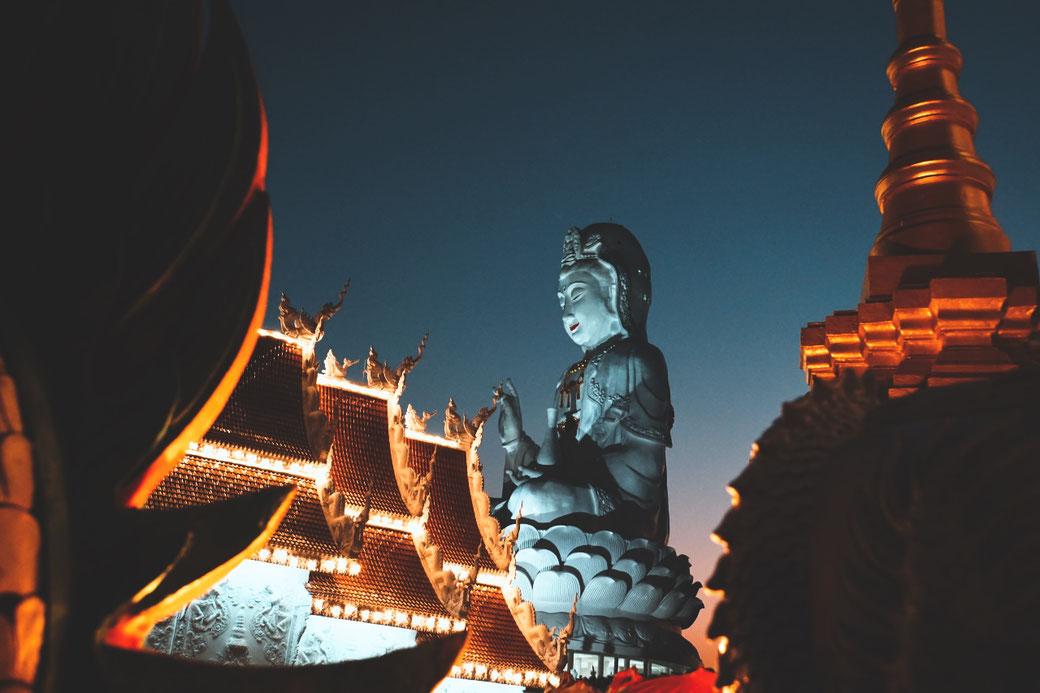 Tempel bei Nacht. Im Hintergrund ein angestrahlter Buddha