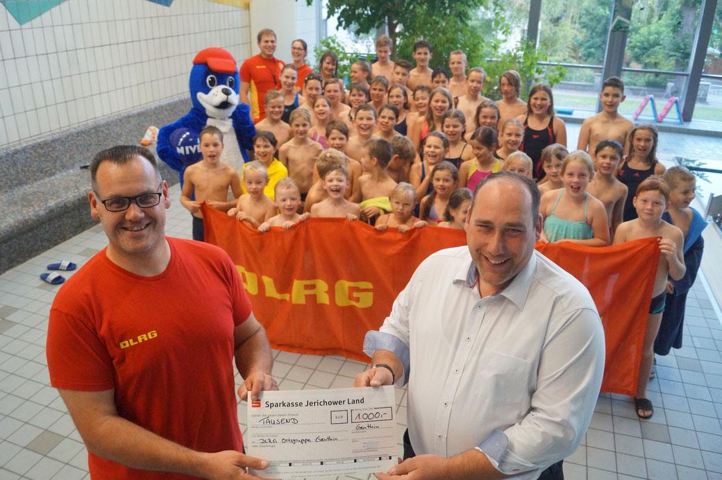 Unternehmer Jens Meißner (rechts) überreicht einen 1000-Euro-Scheck an Andy Gamalski von der Genthiner DLRG-Ortsgruppe. Foto: Alpha-Report