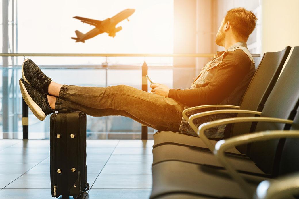 Mann wartet auf den Flug am Flughafen
