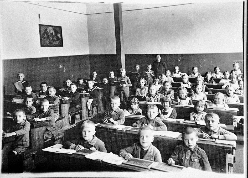 Eine Schulklasse in früherer Zeit. 1960 fand ich in meiner Schule schon bessere Lernverhältnisse vor.