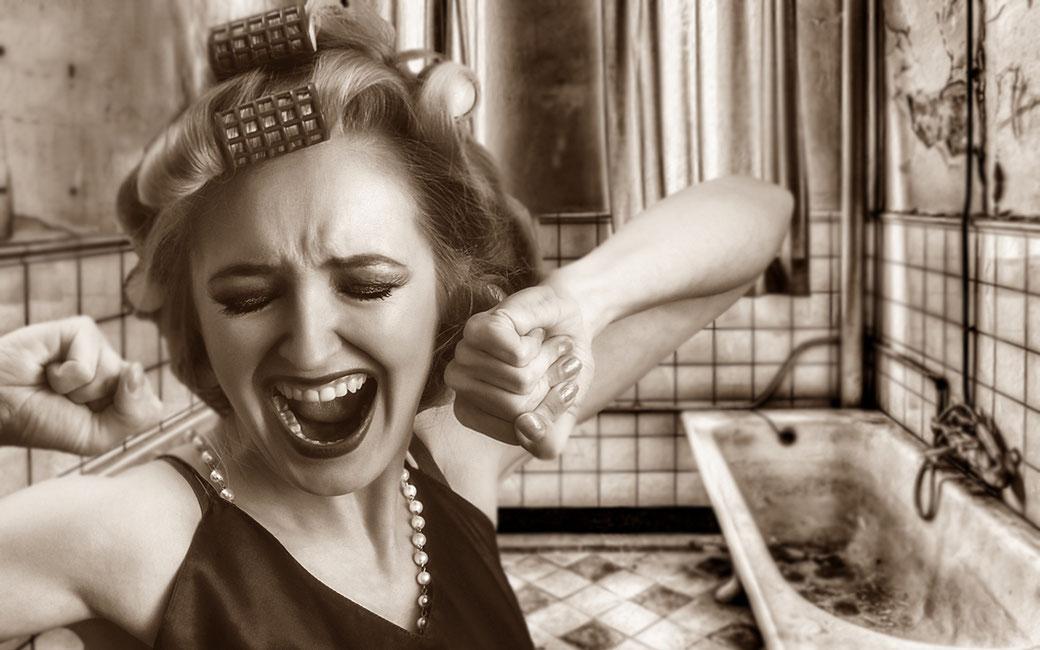 Hausfrau schreit auf über den schlimmen Zustand ihres Badezimmers.