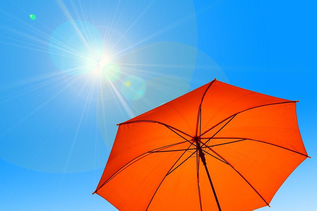 Roter Regenschirm vor blauem Himmel