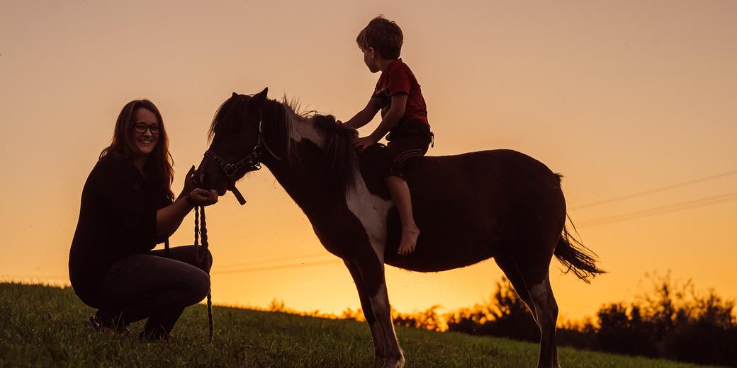 Kind auf Pferd während tiergestützter Therapie