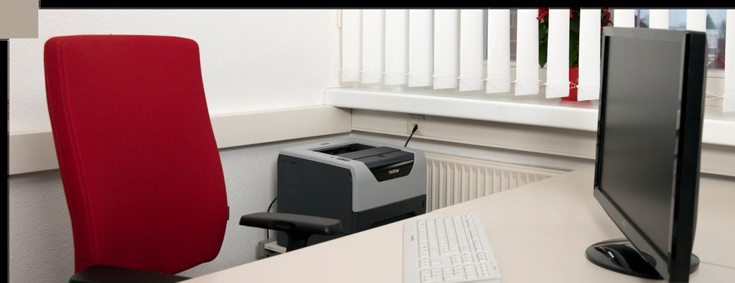 Ein freier roter Schreibtischstuhl am Schreibtisch mit Computer - Symbol für freie Arbeitsplätze