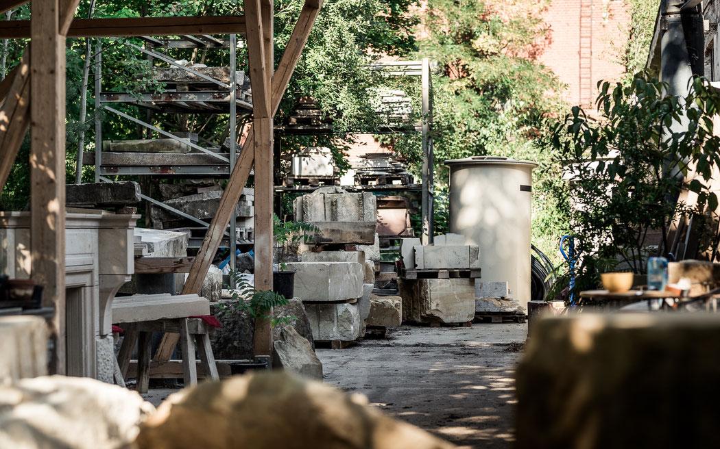 Das Außengelände der Meilenstein Werkstatt in Dresden: Sandstein Blöcke, ein Schauer zum Arbeiten und viele Pflanzen