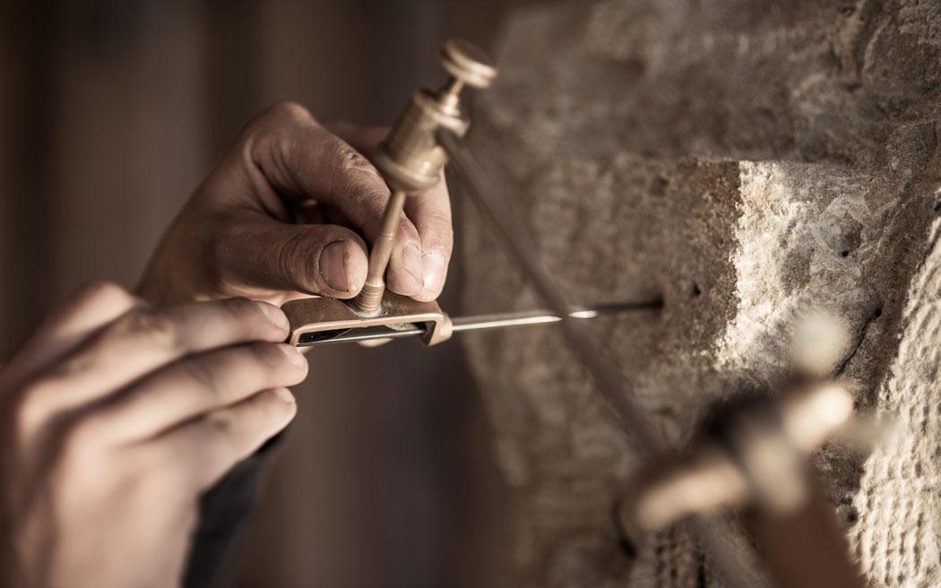 Steinmetz Marcus Scheffczyk arbeitet mit einem Punktiergerät am Sandstein