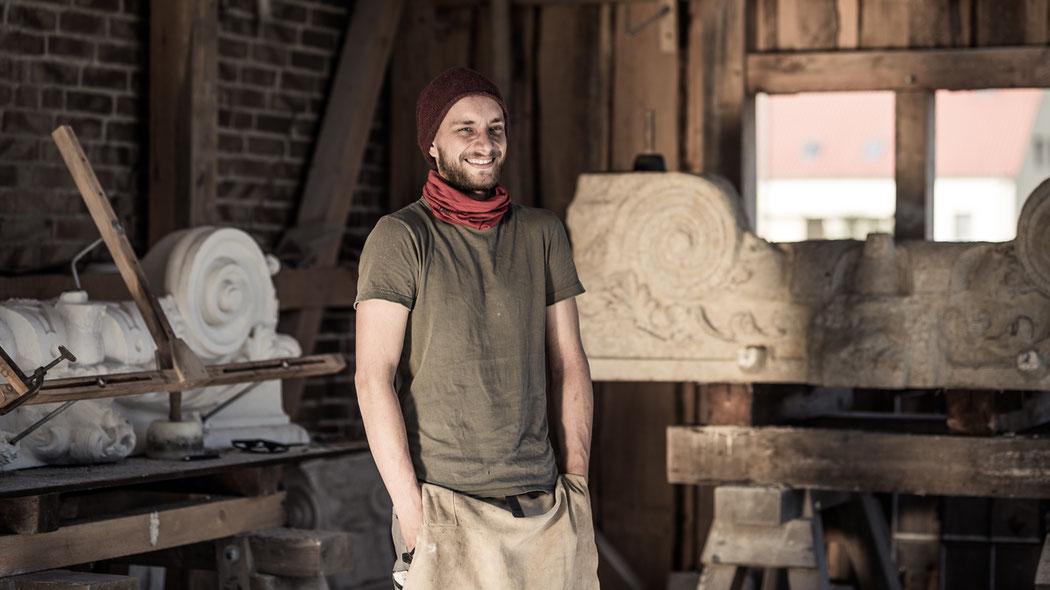 Steinmetz Marcus Scheffczyk steht in Zunftkleidung vor einem Bildhauer-Stück aus Sandstein
