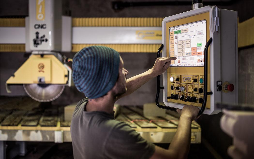Marcus Scheffczyk steht am Bildschirm seiner CNC Säge und programmiert ein Säge-Projekt