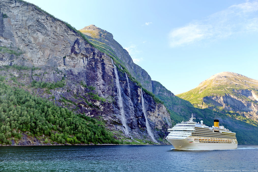 A cruise ship in Geirangerfjord passes the Seven Sisters waterfalls