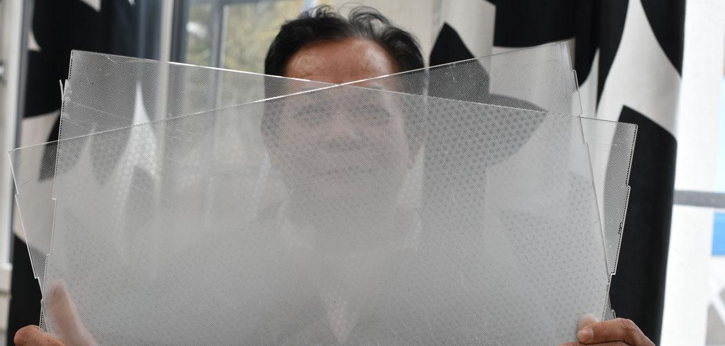 Arbeitnehmer hinter zwei Pexiglas-Scheiben, die aus Bildschirmen entfernt werden