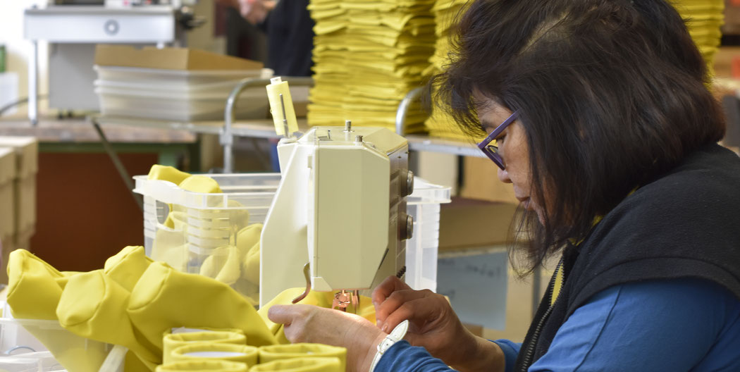 """Arbeitnehmerin beim Nähen eines """"sacco"""" Brillenhalters"""