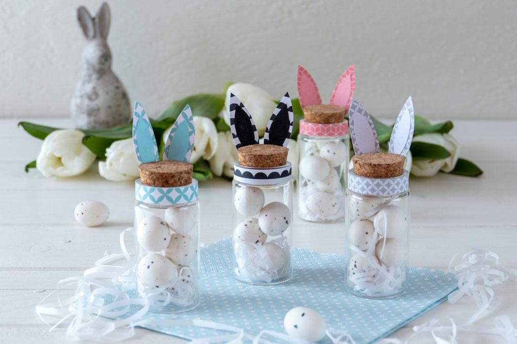 Kleine Gläser mit Korkdeckel gefüllt mit weissem Ostergras und Marzipaneiern