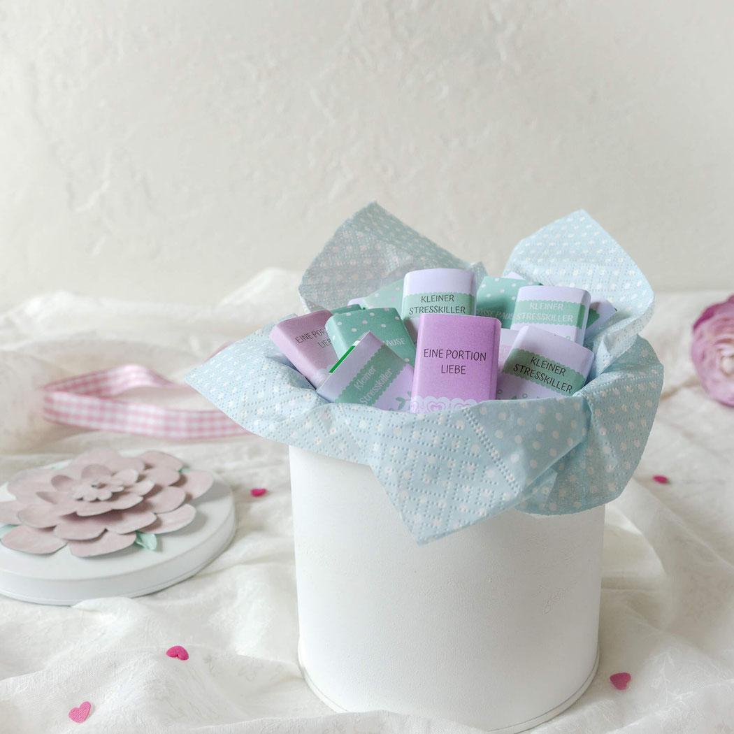 Weisse Dose gefüllt mit kleinen, selber eingepackten Schokoladen