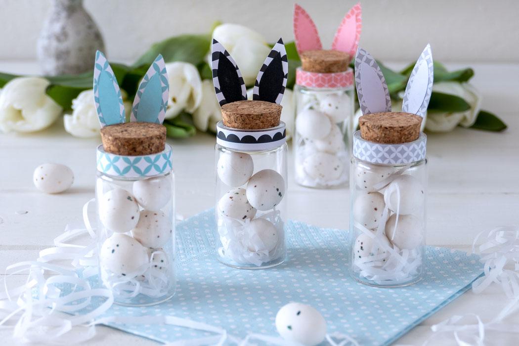 Gläser mit Korkdeckel, Manschette und Hasenohren aus Papier. Gefüllt mit Ostereiern aus Marzipan