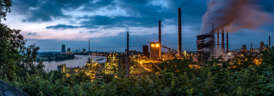 """Alsumer Berg, Panaroma von dem nordöstlichen Aussichtspunkt. Von links nach rechts: Kraftwerk Walsum, Rhein, Kokerei Schwelgern: """"Weiße Seite"""", """"Schwarze Seite"""", Koks Löschturm,"""