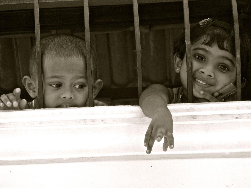 Fort Cochin. Zwei Kids winken mir von oben aus einem vergitterten Wohungsfenster im ersten Stock zu.