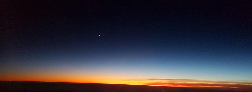Sonnenuntergang mit Mondsichel (bei Vergrößerung über dem Horizont erkennbar) und Sternen (Planeten?), aufgenommen am 27.12.2019 aus dem Flugzeug