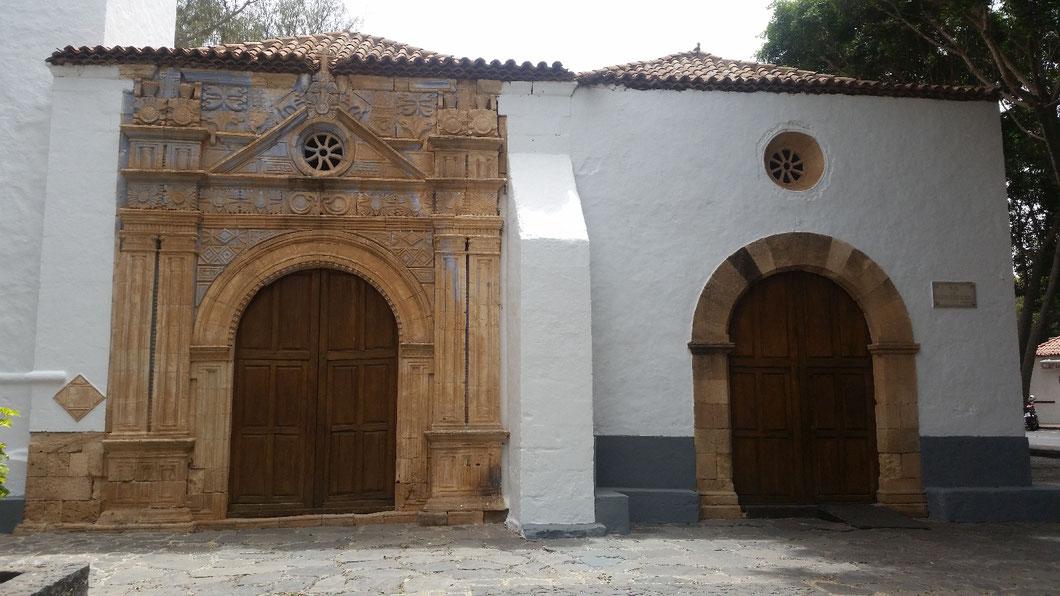 Das hölzerne Hauptportal ist mit Schlangen, Raubkatzen, massenhaften Köpfen und geometrischen Ornamenten verziert. Die Wahl der Motive deutet auf Einflüsse der mittel- oder südamerikanischen Mythologie hin.