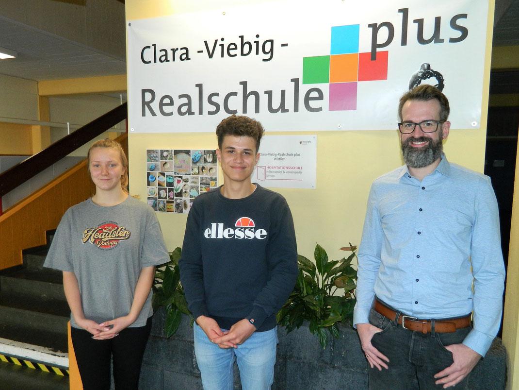 Lisa Servatius und Jean-Philipp Wolff vom Schülersprecherteam gratulieren Philip Herrmann