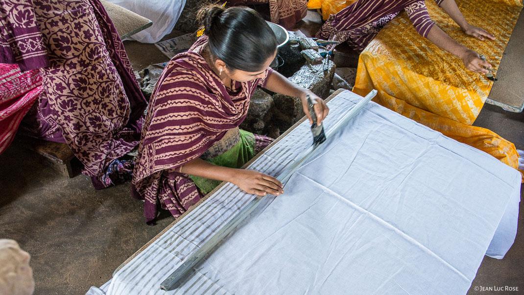 Application d'une cire chaude à l'aide d'une brosse et d'une règle pour réaliser un motif linéaire (Atelier à Bhuj / Gujarat - Inde). LA BOUTIQUE MG, la boutique du tissu artisanal et traditionnel de l'Inde.