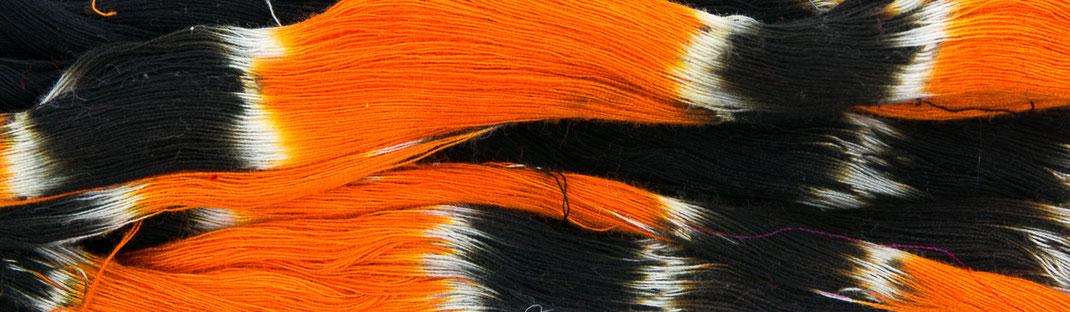 Écheveau débarrassé de ses ligatures après un bain de teinture orange et noire.