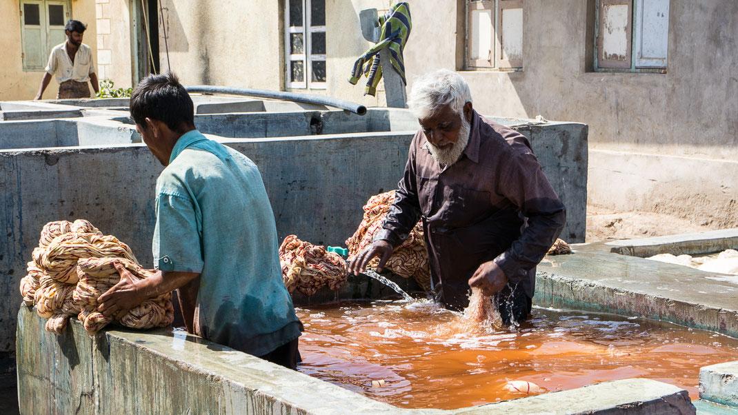 """Lavage à grande eau, avec sur la droite du bassin, la pierre sur laquelle sont """"calandrés"""" les tissus (Gujarat - Inde)."""