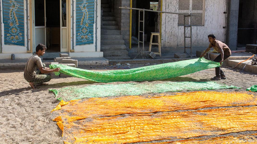 Des tissus batiks, imprimés et colorés, sont étendus sur le sol d'une cour pour être séchés au soleil. LA BOUTIQUE MG, la boutique du tissu artisanal et traditionnel de l'Inde.