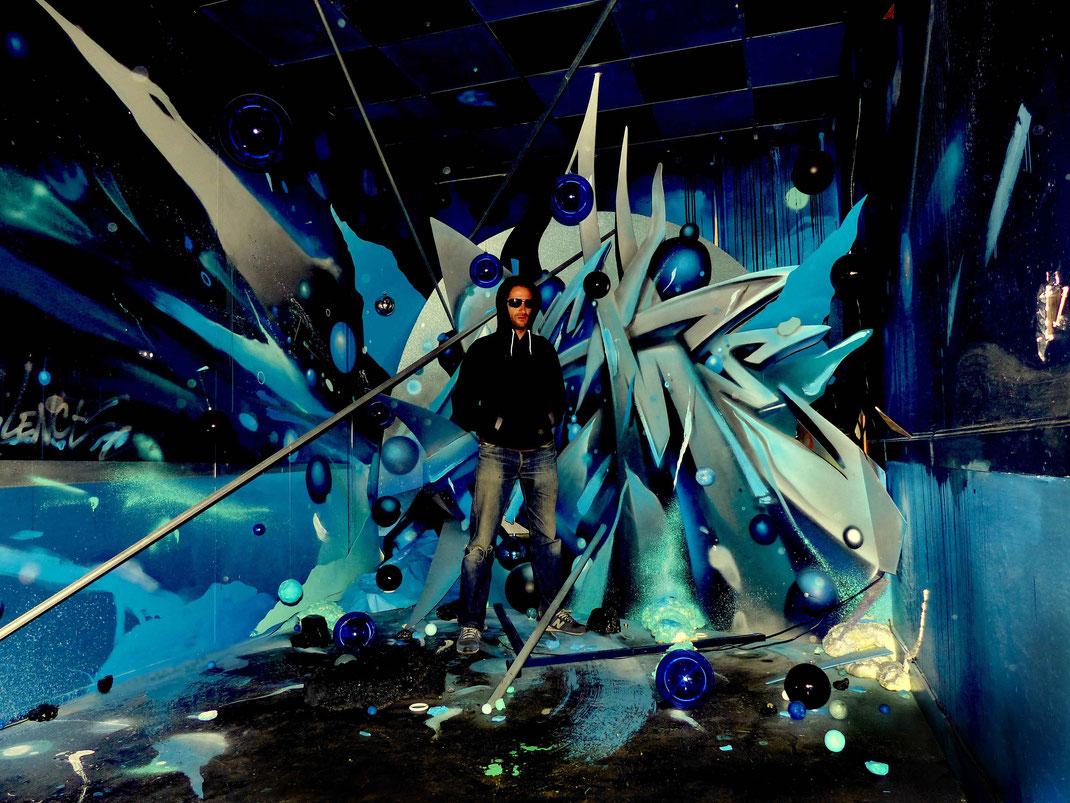 Kendo, graffeur Bordelais posant au centre de son installation lors de l'exposition street art et graffiti TRANSFERT