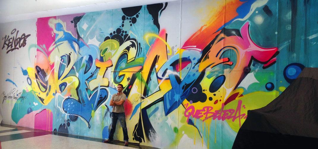Le graffeur Kendo devant sa fresque au centre commercial NATALSHOPPING, au Brésil en 2016.