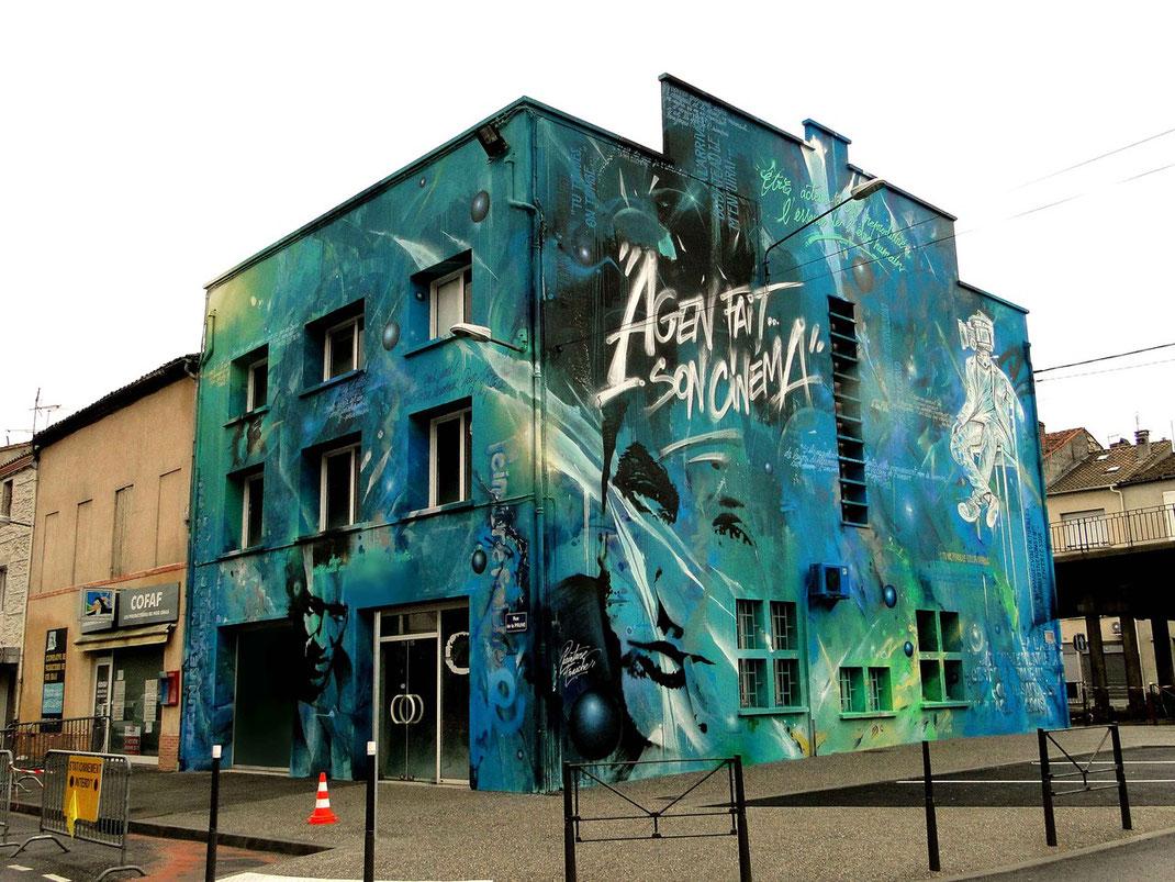Fresque murale street art au cinéma d'agen pour le parcours entre le parking et le cinéma.immeuble bleu de 3étages avec les portraits de Cassel et Penn
