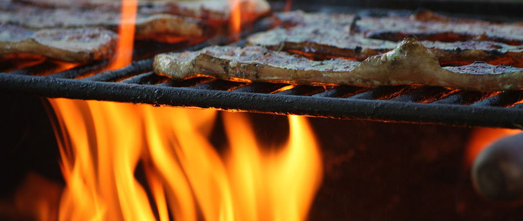 """Meat fillets being grilled"" by Manuel QC – La llama de la barbacoa. Licensed under CC BY-SA 2.0 via Wikimedia Commons."