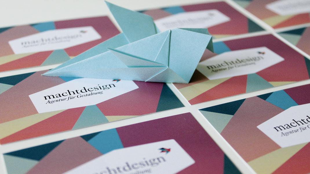 Viele Visitenkarten von machtdesign liegen auf dem Tisch, darauf ein gefaltetes Origami im Stil eines Vogel in Hellbau.