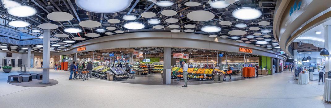 Der neue Eingangsbereich mit dem Lichthof links, der grossen Eingangsfront des Migros Supermarkts und rechts der neue Verbindungsgang zum Surseepark III (u.a. COOP)