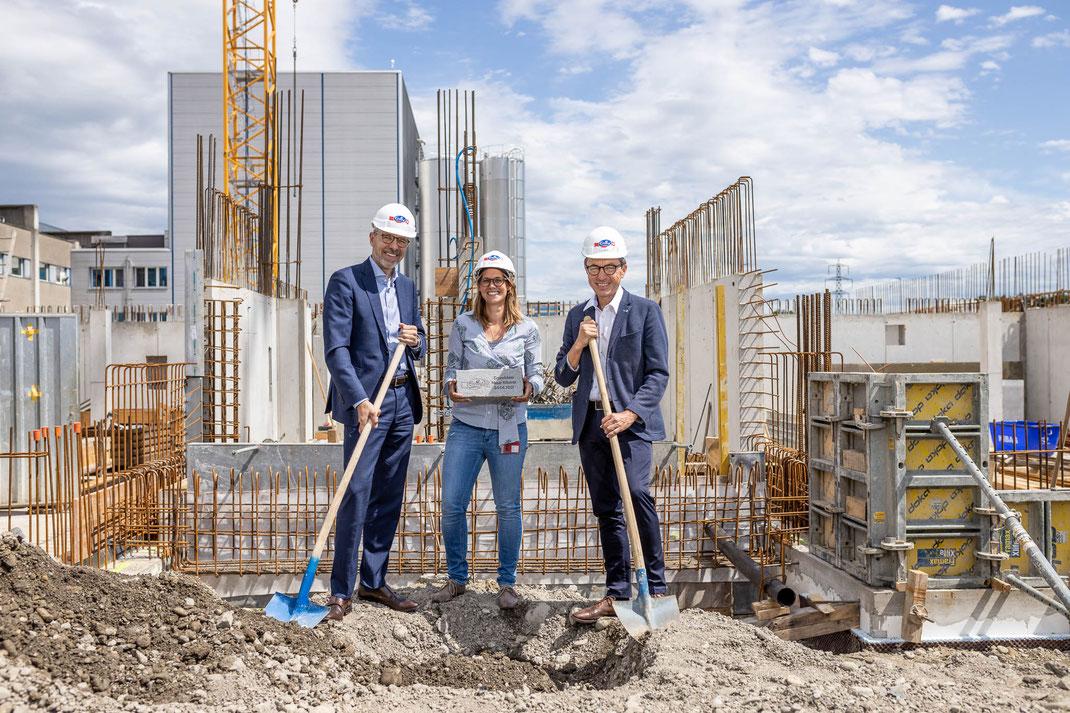 Emmi-Schweiz-Chef Marc Heim (links), Ann-Kathrin Kleinthomä, Projektleiterin und Josef Wyss, Leiter Geschäftsbereich Käse, bei der Grundsteinlegung.