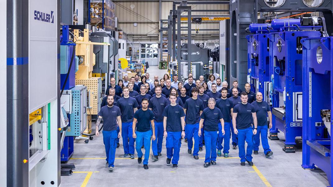 Das Team der Beutler Nova AG zwischen ihrer riesigen Pressen in einer ihrer Produktionshallen in Gettnau/LU