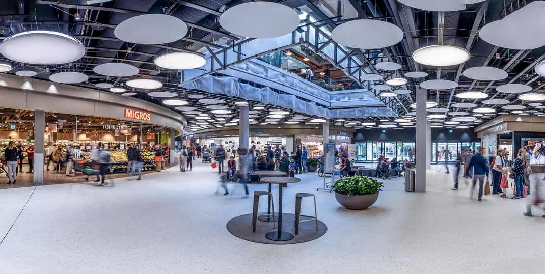 Der neugestaltete Eingangsbereich mit dem neuen Lichthof, der grossen Eingangsfront des Migros Supermarkts und dem Haupteingang.