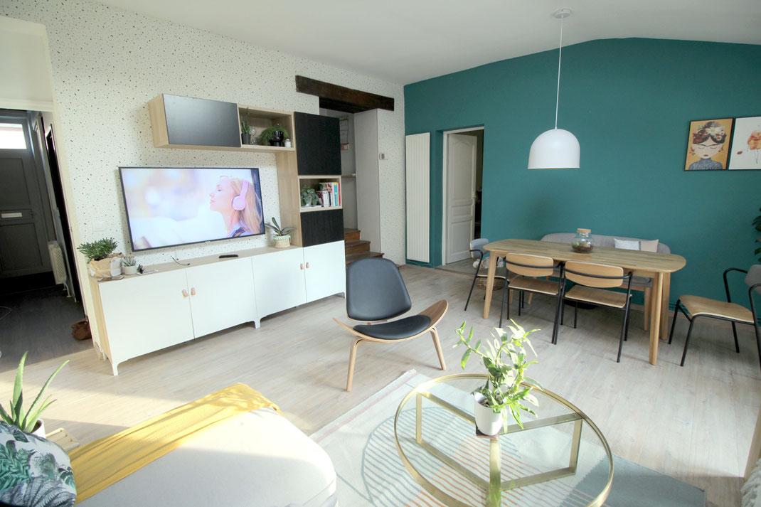 Aménagement d'intérieur, mur bleu vert, meuble tv bibliothèque, siège design, chaises d'écolier, papier peint terrazzo