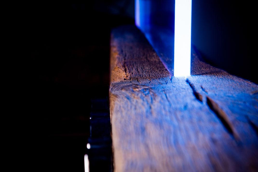 Leuchtende Kanten des Glaselementes, eingelassen in einen Fachwerkbalken. Firmenlogo in Chrom.
