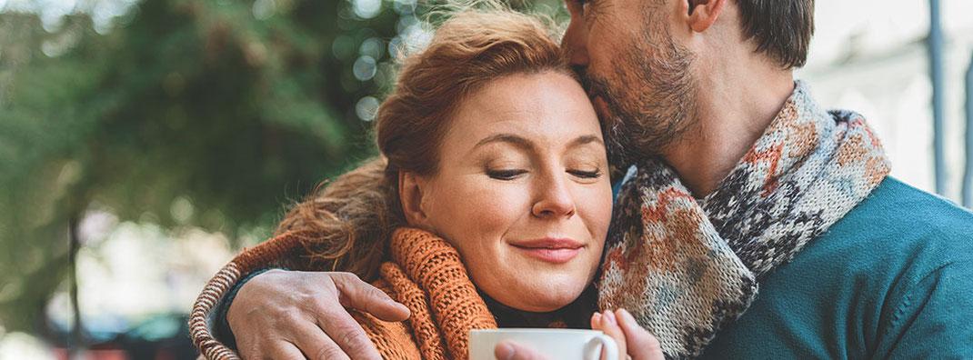 Paar mittleren Alters mit Kaffeetasse, der Mann hat einen Arm um die Frau gelegt, die Frau lächelt mit geschlossenen Augen