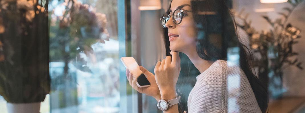 Frau mit Brille sitz am Fenster eines Cafés und hat Handy in der Hand