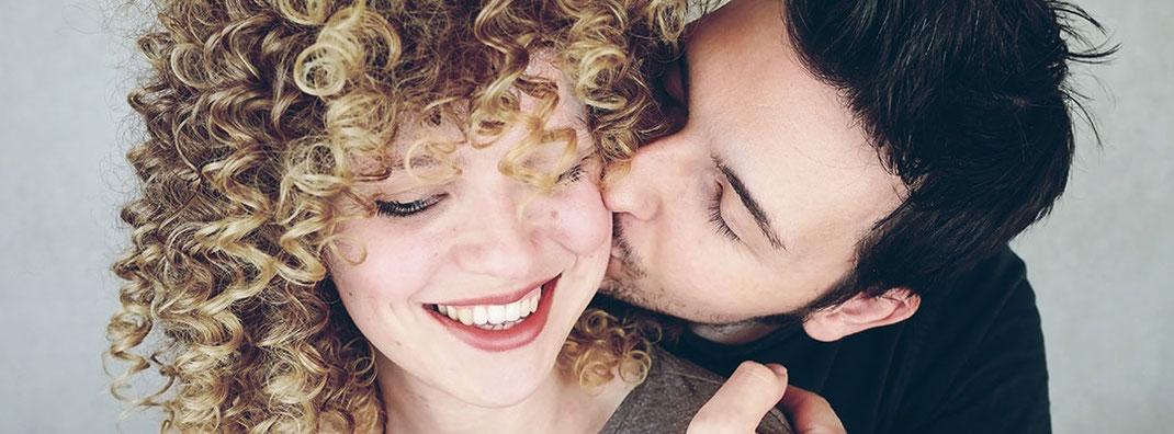 Jugendliches Paar, der Mann umarmt die lächelnde Frau und gibt ihr einen Kuss auf die Wange