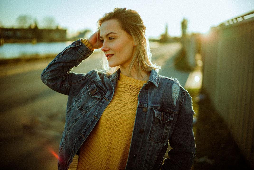 Gegenlichtaufnahme einer jungen Frau mit Jeansjacke und gelben Pullover