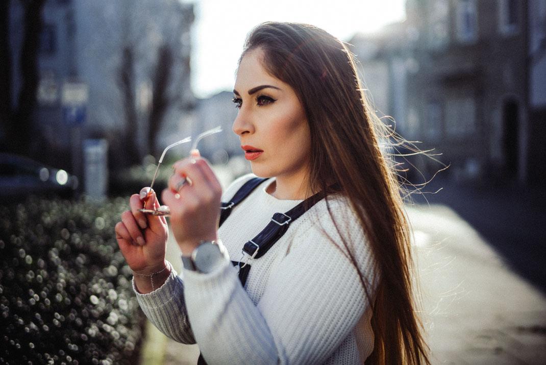 Stylische junge Frau mit Sonnenbrille in der Hand