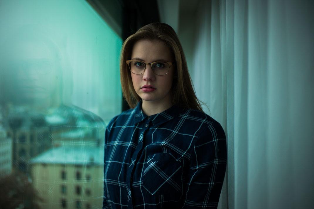 Junge Frau mit stylischer Brille und schickem Hemd