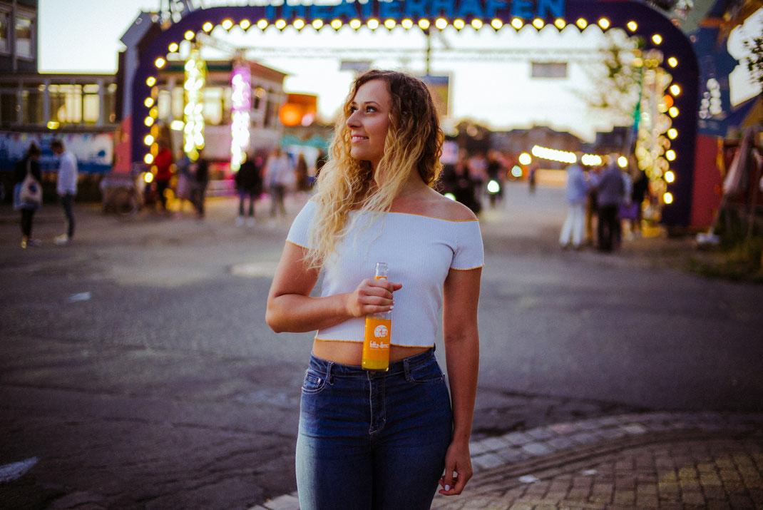 Frau mit Getränk in der Hand im Hintergrund viele bunte Lichter